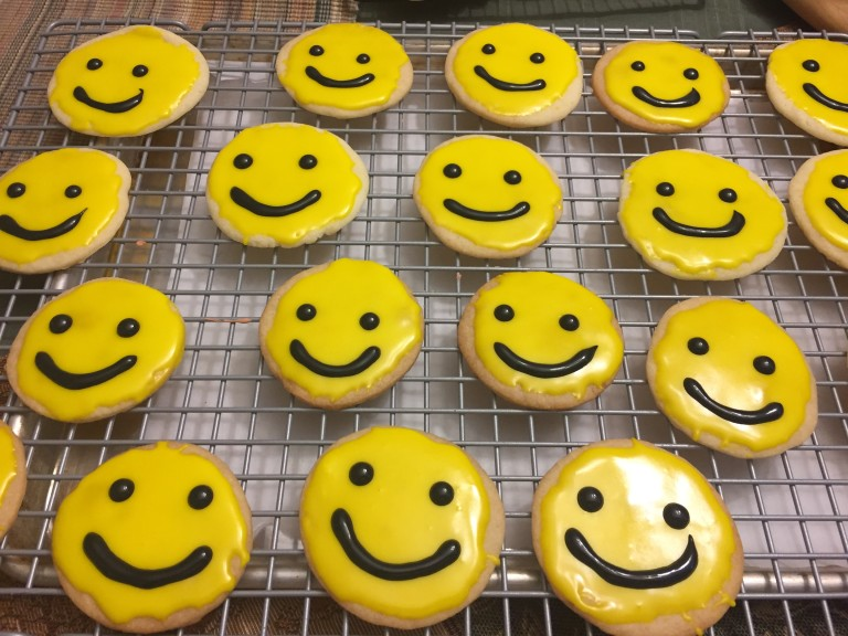 photo of iced cutout cookies with smiley faces from cocos confections